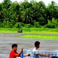 Warga mengendarai sepeda motor bersama anak kecil melintasi landasan pacu Bandara Binaka | Etis Nehe