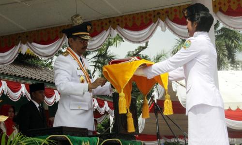 Tania Kristin Zebua menerima bendera dari Plt Gubsu Tengku Erry Nuradi pada upacara HUT RI ke-70 Provinsi Sumut | sumutprov.go.id