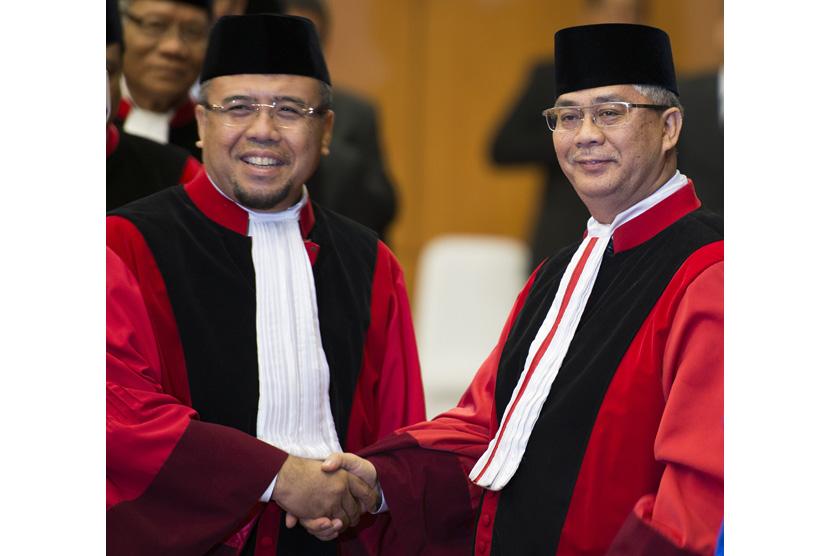 Akil Mochtar dan Patrialis Akbar berjabat tanggan usai pengucapan sumpah jabatan Akil sebagai Ketua MK di Gedung MK, Jakarta, Selasa, 20/8/2013 |ANTARA FOTO/Widodo S. Jusuf